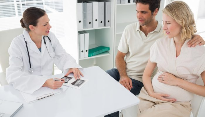 High angle view of female gynaecologist explaining reports to expectant couple in clinic