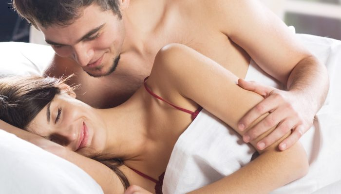 Young beautiful amorous couple making love in bed