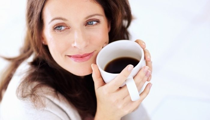 Happy woman having coffee looking away in thought