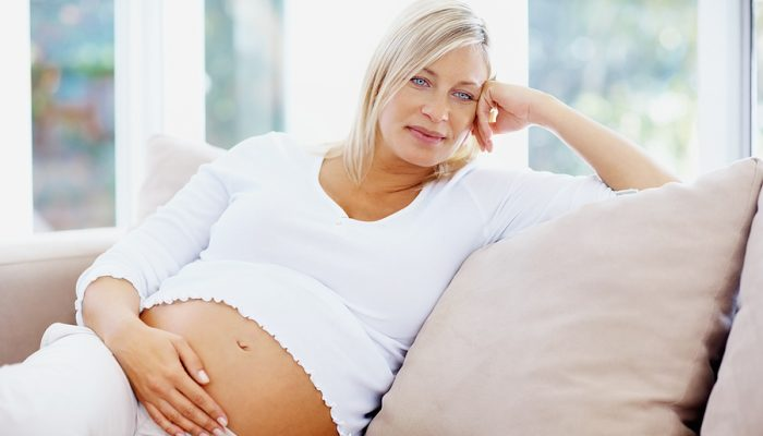 Thoughtful middle aged pregnant woman relaxing on couch at home