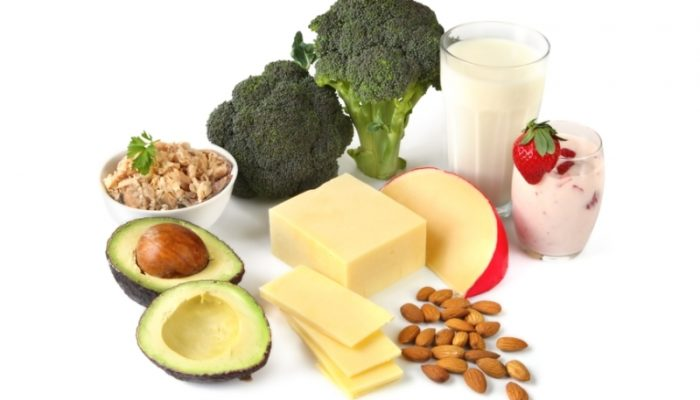 Calcium-rich foods, on white background. Includes avocado, salmon, broccoli, milk, yoghurt, cheeses, and almonds.