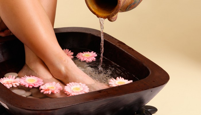 Water pouring from an earthenware pot into a luxurious aromatic foot soak