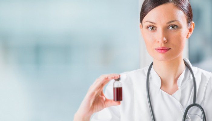 Portrait of pretty female laboratory assistant analyzing a blood sample at hospital