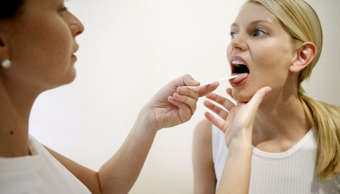 Doctor examining female patient with tongue depressor --- Image by © Royalty-Free/Corbis
