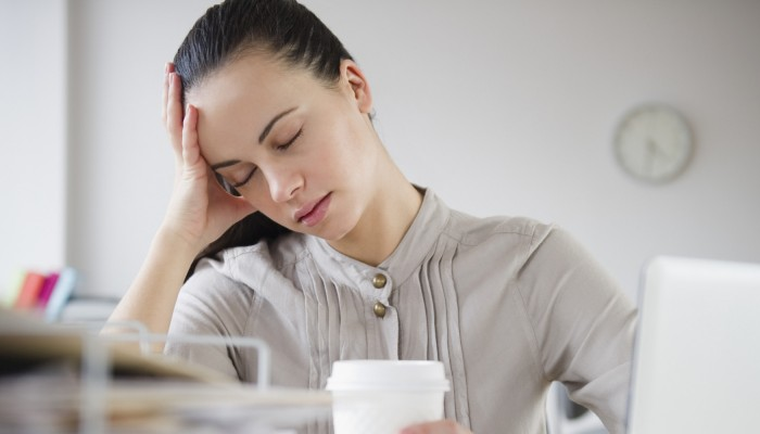 Woman exhausted at desk with coffee