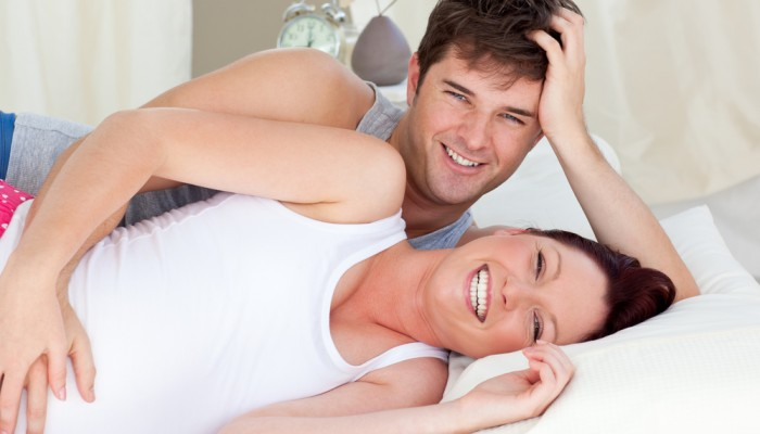 Laughing caucasian pregnant woman lying on bed with her husband in the bedroom