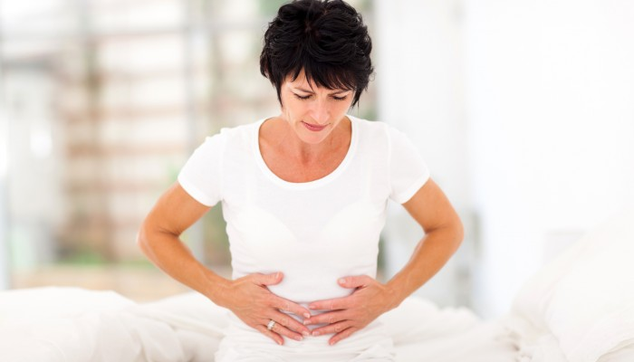 mid age woman having stomach pain at home