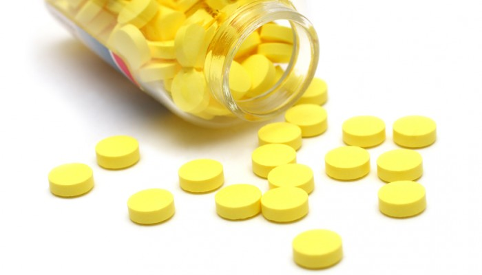 yellow pills around transparent bottle on white background